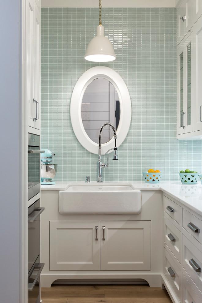 Idées déco pour une petit cuisine bord de mer en U avec un évier de ferme, un placard à porte shaker, des portes de placard blanches, une crédence bleue, une crédence en carreau de verre, un sol en bois clair et un plan de travail blanc.
