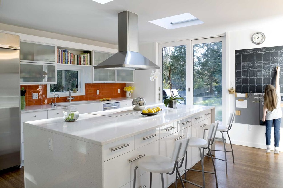 Example of a trendy galley kitchen design in New York with a farmhouse sink, glass-front cabinets, white cabinets, quartz countertops, orange backsplash, stainless steel appliances and glass tile backsplash