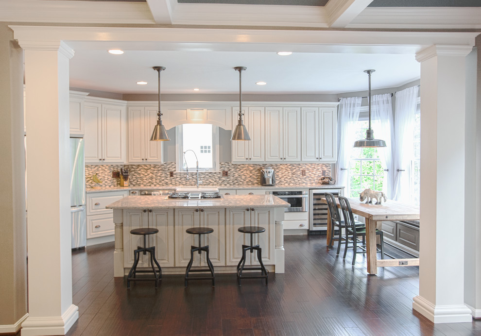 Example of a mid-sized cottage l-shaped dark wood floor eat-in kitchen design in DC Metro with a farmhouse sink, white cabinets, granite countertops, multicolored backsplash, mosaic tile backsplash, stainless steel appliances, raised-panel cabinets and an island