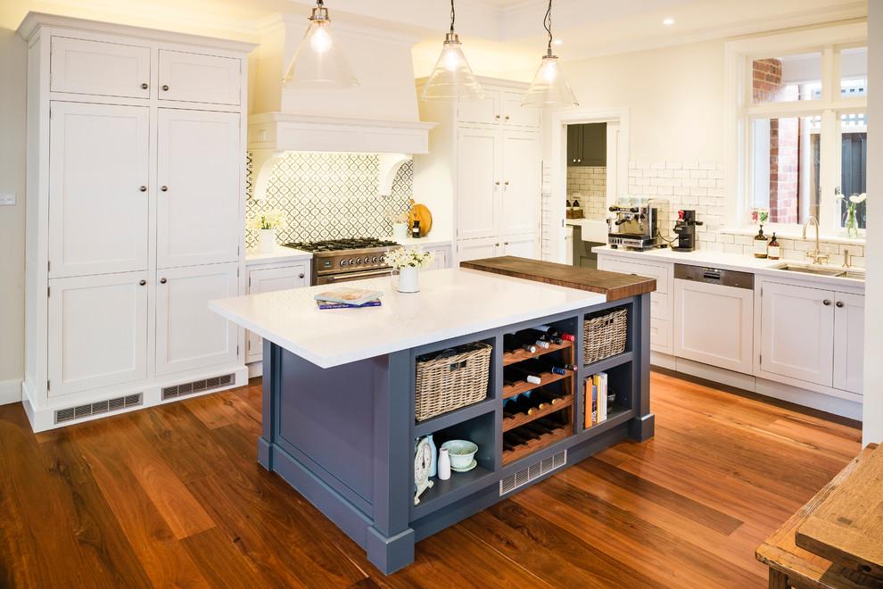 Inspiration for a timeless l-shaped kitchen remodel in Melbourne with a double-bowl sink, shaker cabinets, white cabinets, beige backsplash, subway tile backsplash and paneled appliances