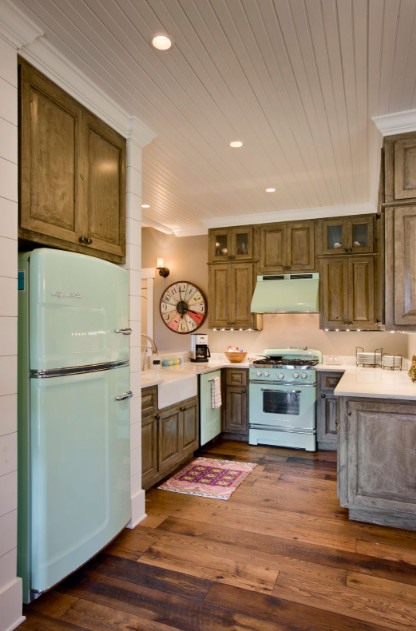 Inspiration for a mid-sized country u-shaped dark wood floor enclosed kitchen remodel in Other with a farmhouse sink, raised-panel cabinets, dark wood cabinets, quartzite countertops, white backsplash, colored appliances and no island