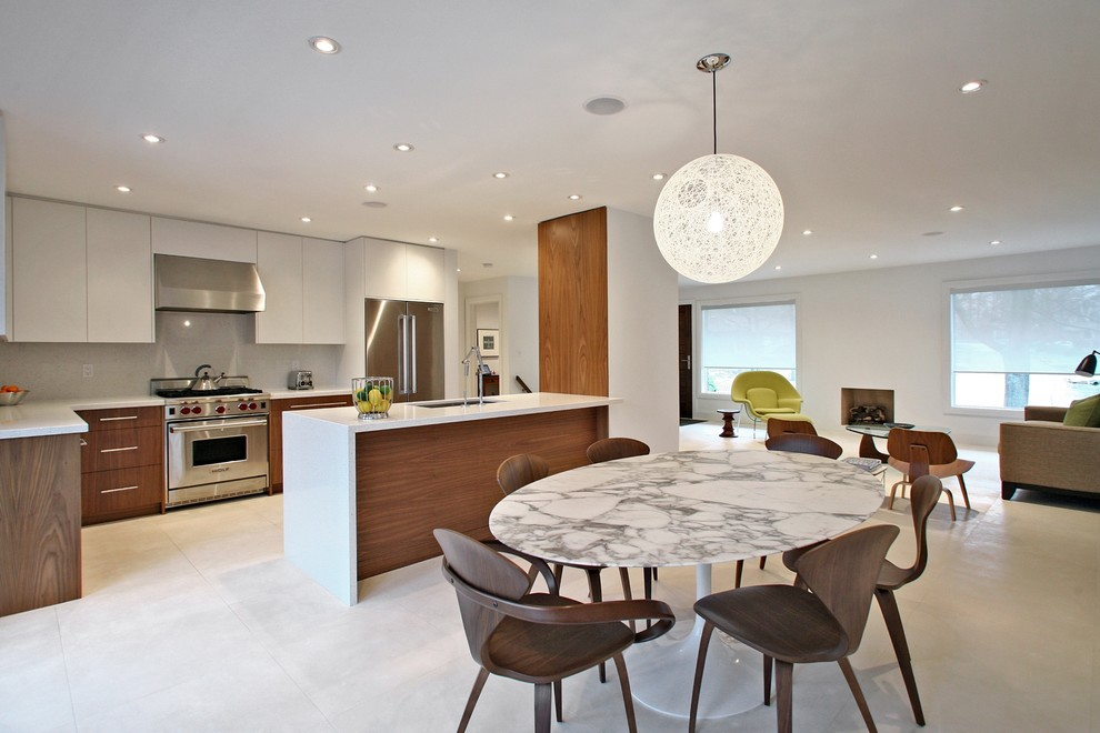Example of a minimalist galley open concept kitchen design in Toronto with an undermount sink, dark wood cabinets, flat-panel cabinets, white backsplash and stainless steel appliances