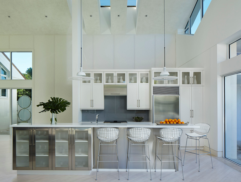 Mid-sized trendy single-wall light wood floor and beige floor open concept kitchen photo in Miami with shaker cabinets, white cabinets, gray backsplash, stainless steel appliances, an island, quartz countertops and glass sheet backsplash