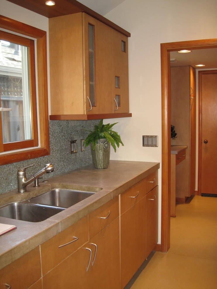 Mid-sized galley concrete floor enclosed kitchen photo in San Francisco with an undermount sink, flat-panel cabinets, light wood cabinets, concrete countertops, green backsplash, cement tile backsplash and stainless steel appliances