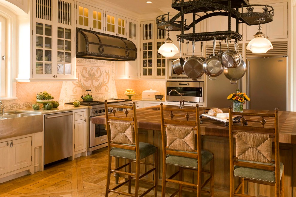 Mid-sized tuscan l-shaped medium tone wood floor eat-in kitchen photo in Denver with a farmhouse sink, raised-panel cabinets, beige cabinets, wood countertops, beige backsplash, stainless steel appliances, an island and mosaic tile backsplash