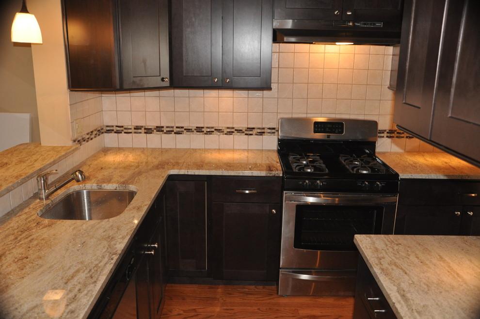 Kitchen - small contemporary l-shaped medium tone wood floor kitchen idea in Philadelphia with an undermount sink, shaker cabinets, dark wood cabinets, granite countertops, white backsplash, ceramic backsplash and stainless steel appliances