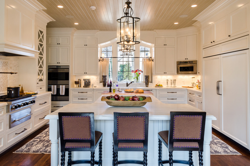 Large elegant u-shaped dark wood floor eat-in kitchen photo in Nashville with recessed-panel cabinets, white cabinets, marble countertops, gray backsplash, stone tile backsplash, stainless steel appliances and an island