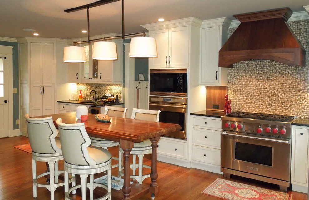 Inspiration for a mid-sized timeless l-shaped medium tone wood floor open concept kitchen remodel in Charleston with an undermount sink, beaded inset cabinets, white cabinets, granite countertops, multicolored backsplash, stone tile backsplash, stainless steel appliances and an island