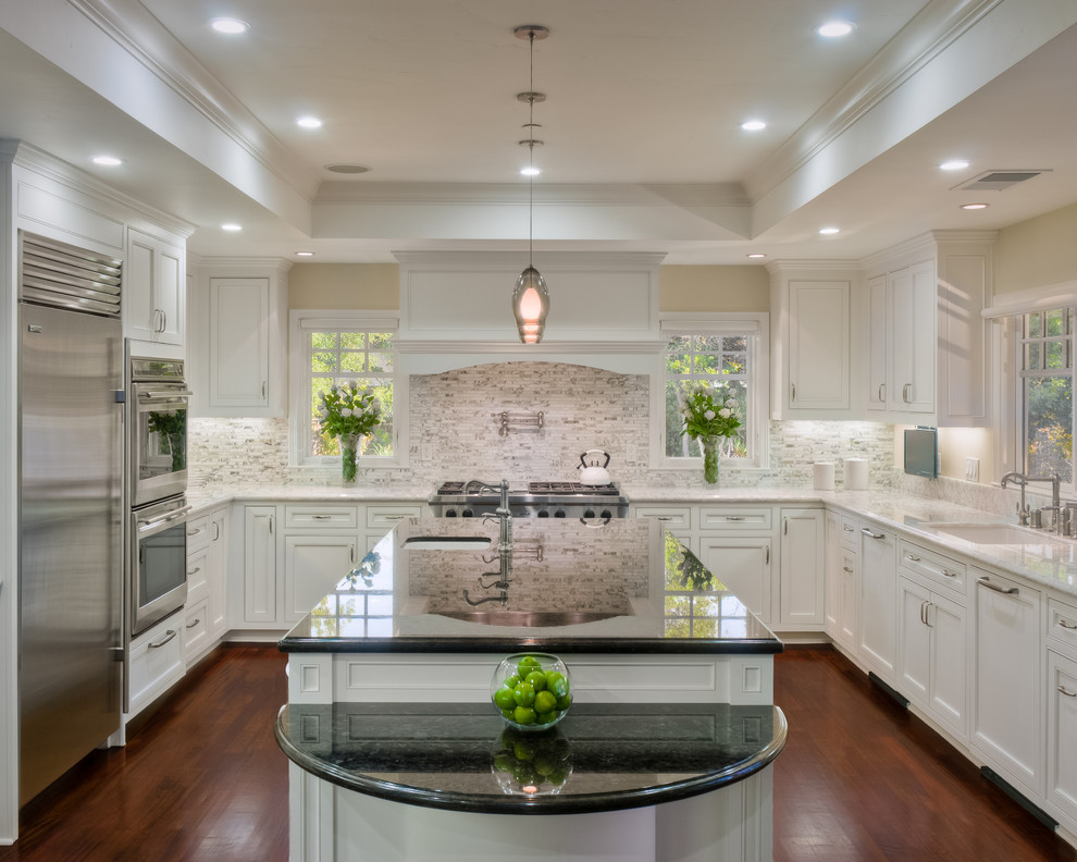 Example of a classic u-shaped dark wood floor kitchen design in San Francisco with stone tile backsplash, granite countertops, an undermount sink, recessed-panel cabinets, white cabinets, white backsplash, stainless steel appliances and an island