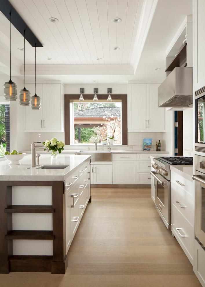 Modelo de cocinas en L de estilo de casa de campo, abierta, con fregadero sobremueble, armarios estilo shaker, puertas de armario amarillas, electrodomésticos de acero inoxidable, suelo de madera clara y una isla