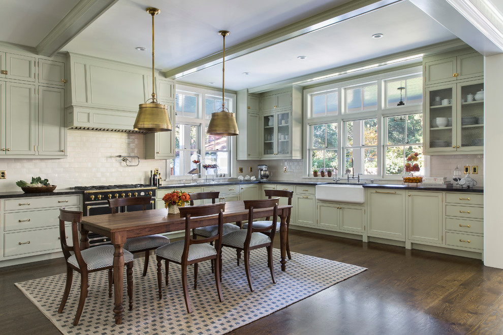 Inspiration for a mid-sized transitional l-shaped dark wood floor and brown floor eat-in kitchen remodel in San Francisco with a farmhouse sink, recessed-panel cabinets, green cabinets, white backsplash, black appliances, solid surface countertops, porcelain backsplash and an island