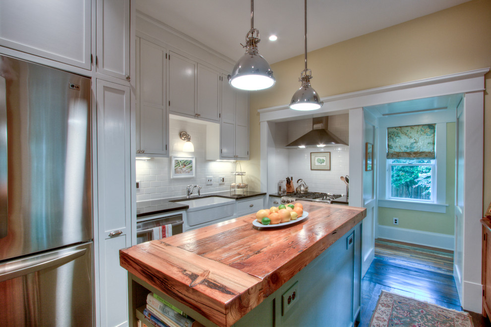 Arts and crafts l-shaped enclosed kitchen photo in Atlanta with a farmhouse sink, recessed-panel cabinets, white cabinets, granite countertops, white backsplash, subway tile backsplash and stainless steel appliances