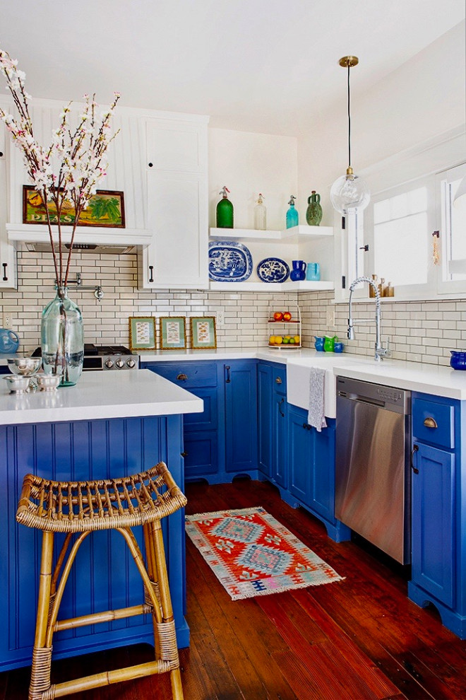 Mid-sized arts and crafts l-shaped dark wood floor and brown floor enclosed kitchen photo in Los Angeles with a farmhouse sink, shaker cabinets, blue cabinets, quartz countertops, white backsplash, ceramic backsplash, stainless steel appliances, an island and white countertops