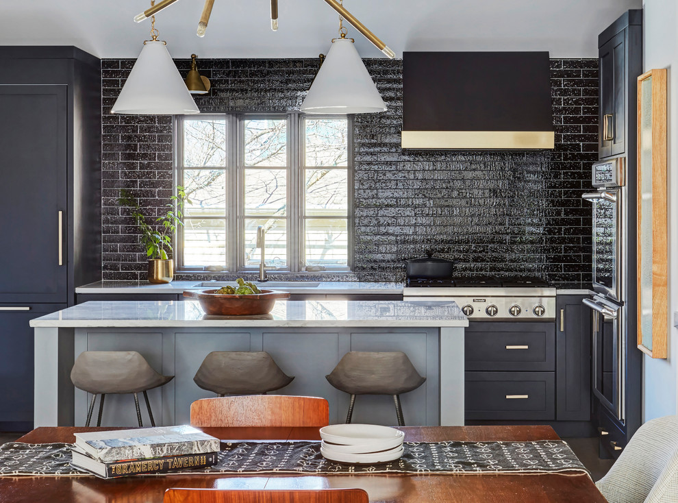 Inspiration for a transitional l-shaped kitchen remodel in Chicago with an undermount sink, shaker cabinets, black cabinets, an island and white countertops