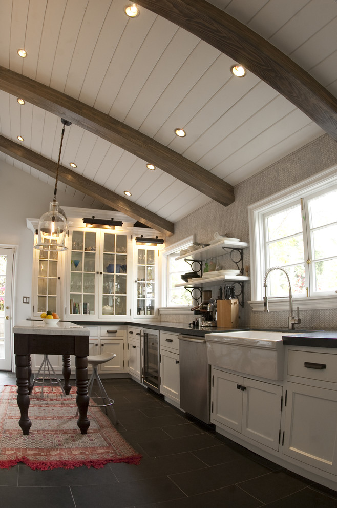 Example of a mountain style kitchen design in Los Angeles with glass-front cabinets, stainless steel appliances, a farmhouse sink and white cabinets