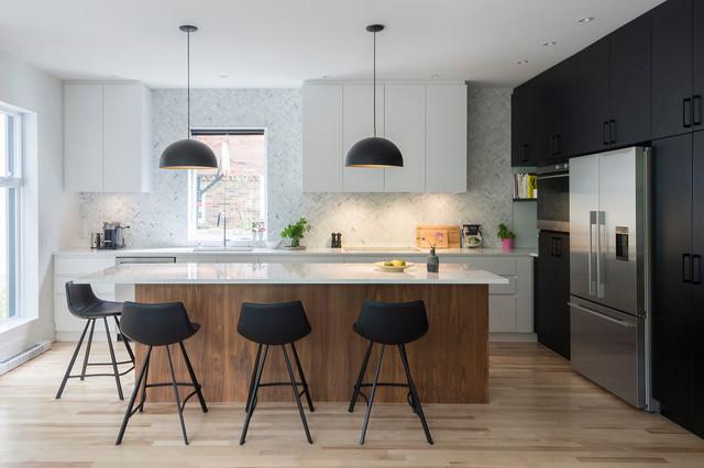 Inspiration pour une cuisine design en L avec un évier 1 bac, un placard à porte plane, des portes de placard noires, une crédence blanche, un électroménager en acier inoxydable, un sol en bois clair et un îlot central.