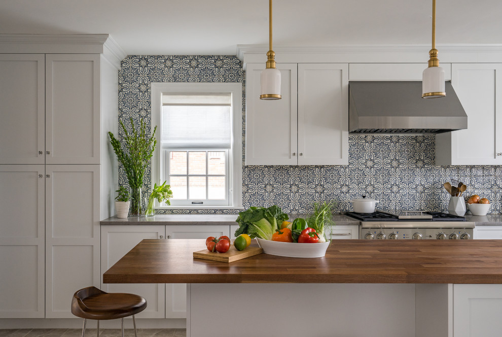 Example of a trendy u-shaped gray floor enclosed kitchen design in Boston with a farmhouse sink, shaker cabinets, white cabinets, stainless steel appliances, an island, wood countertops, multicolored backsplash and ceramic backsplash