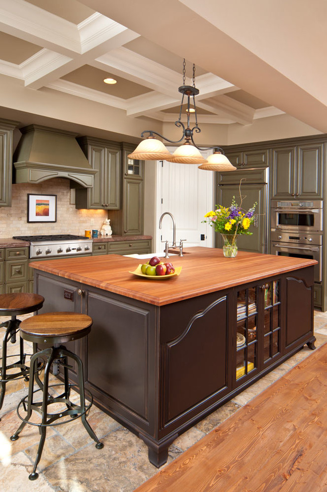 Kitchen - traditional kitchen idea in Other with raised-panel cabinets, green cabinets, beige backsplash, stainless steel appliances and an island