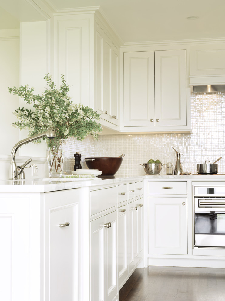 Inspiration for a timeless kitchen remodel in Boston with stainless steel appliances, recessed-panel cabinets, white cabinets and white backsplash