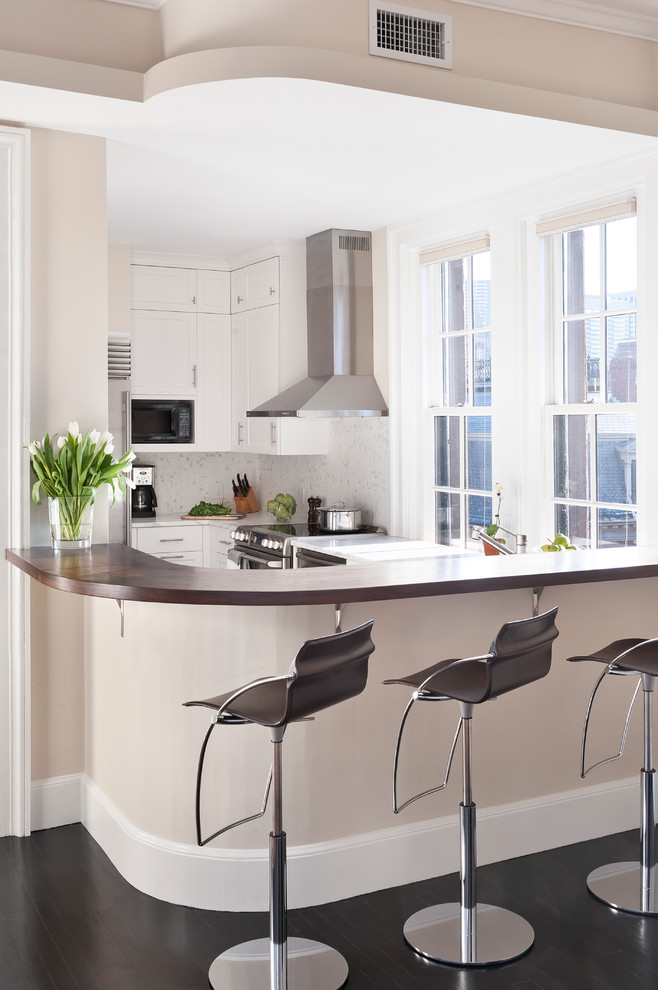 Example of a transitional u-shaped enclosed kitchen design in Boston with stainless steel appliances, white cabinets and white backsplash