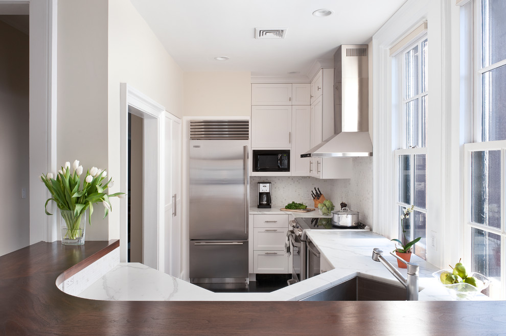 Trendy enclosed kitchen photo in Boston with stainless steel appliances, shaker cabinets, white cabinets and white backsplash