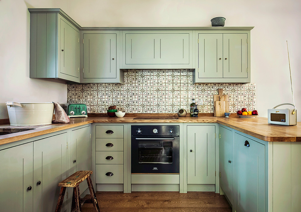 Inspiration for a country u-shaped medium tone wood floor kitchen remodel in London with an undermount sink, beaded inset cabinets, green cabinets, wood countertops, green backsplash, mosaic tile backsplash and black appliances