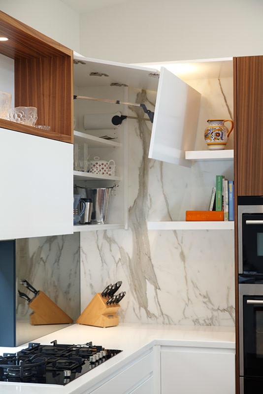 Immagine di una cucina moderna di medie dimensioni con ante lisce, ante in legno scuro, top in marmo, paraspruzzi a effetto metallico, paraspruzzi a specchio, elettrodomestici in acciaio inossidabile, pavimento in legno massello medio e un'isola