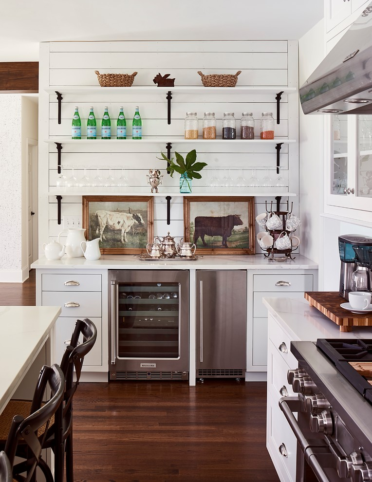 Inspiration for a farmhouse l-shaped dark wood floor and brown floor kitchen remodel in Charlotte with flat-panel cabinets, white cabinets, white backsplash, subway tile backsplash and stainless steel appliances