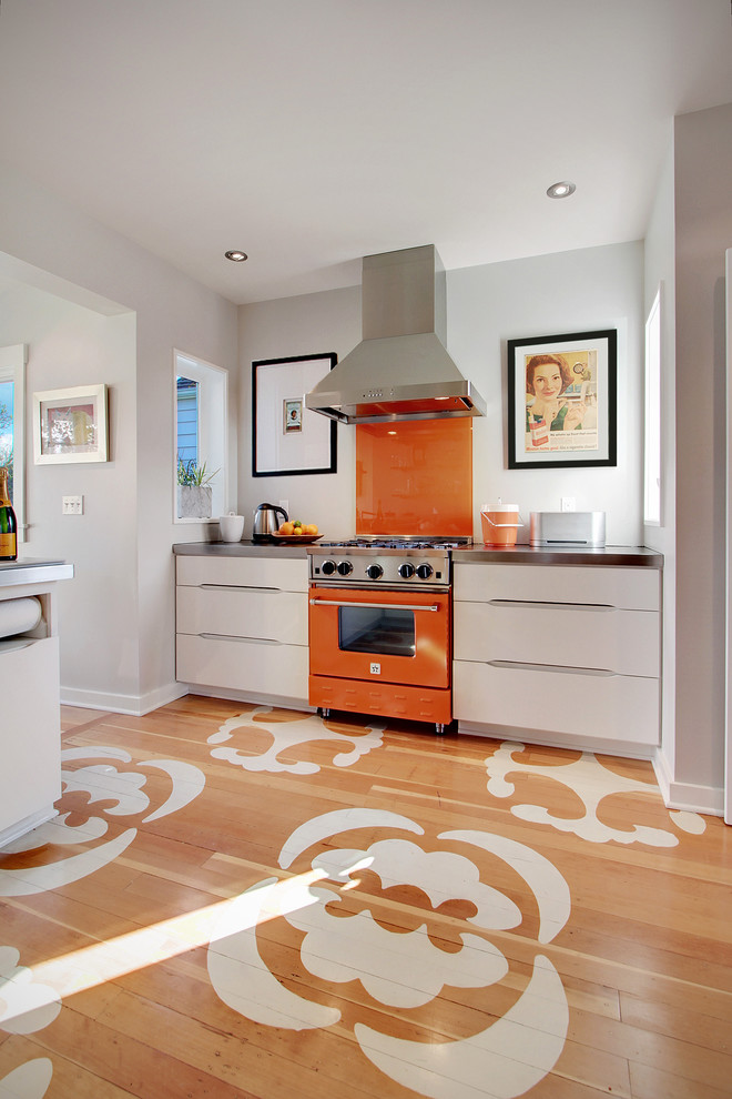 Enclosed kitchen - contemporary painted wood floor and multicolored floor enclosed kitchen idea in Seattle with flat-panel cabinets, white cabinets, orange backsplash, glass sheet backsplash, colored appliances and zinc countertops