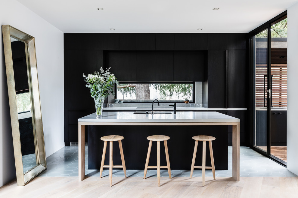 Trendy galley beige floor kitchen photo in Melbourne with an undermount sink, flat-panel cabinets, black cabinets, window backsplash, paneled appliances, an island and gray countertops