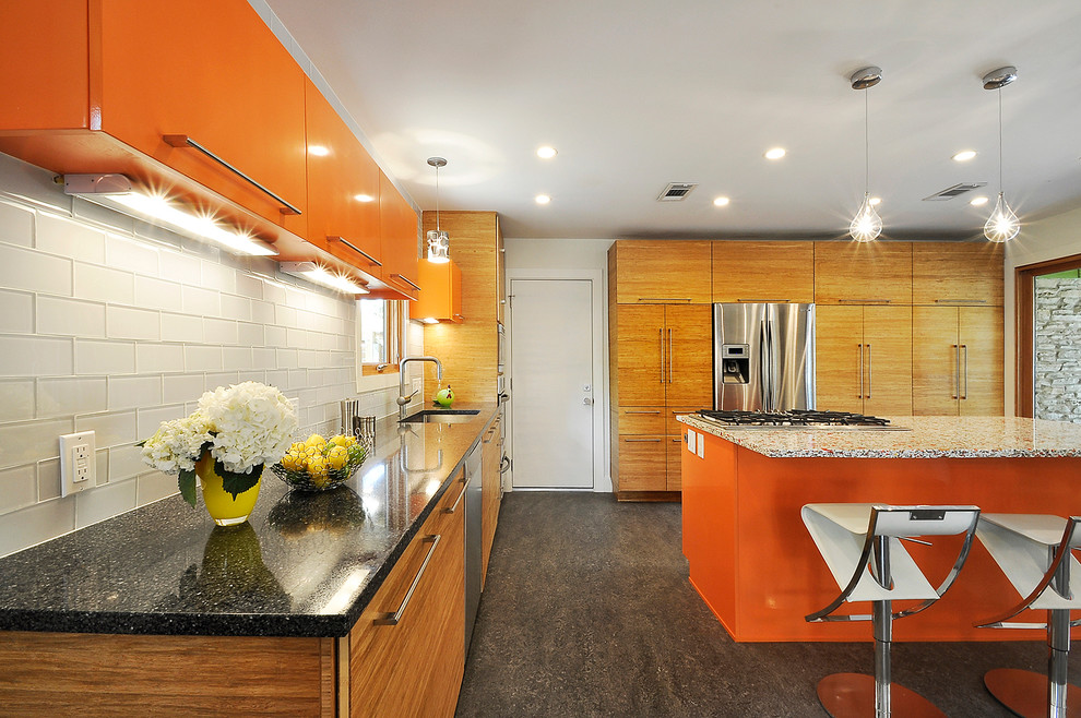 Example of an eclectic kitchen design in Austin with an undermount sink, flat-panel cabinets, orange cabinets, white backsplash, glass tile backsplash and stainless steel appliances