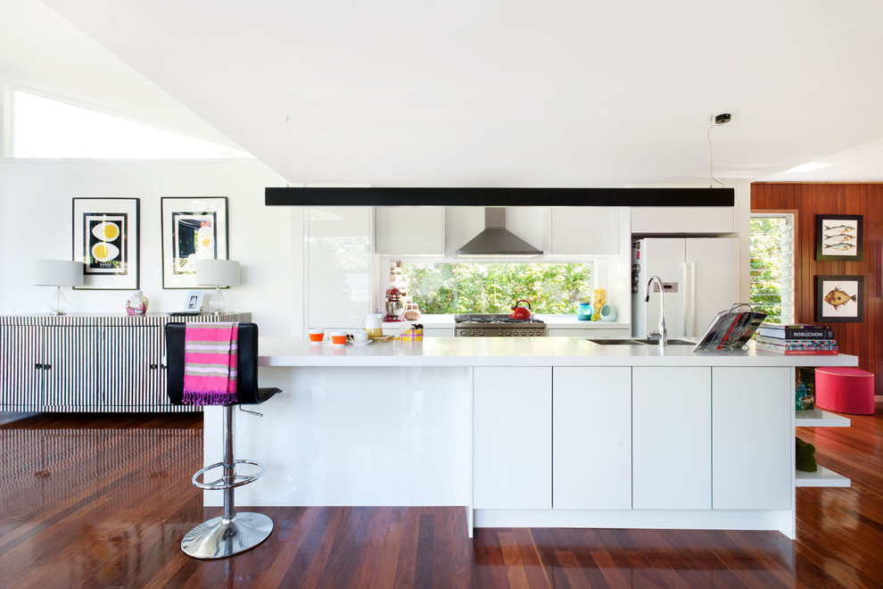 Design ideas for a mid-sized contemporary galley eat-in kitchen in Brisbane with flat-panel cabinets, white cabinets, window splashback, stainless steel appliances, dark hardwood floors, brown floor, a double-bowl sink and an island.