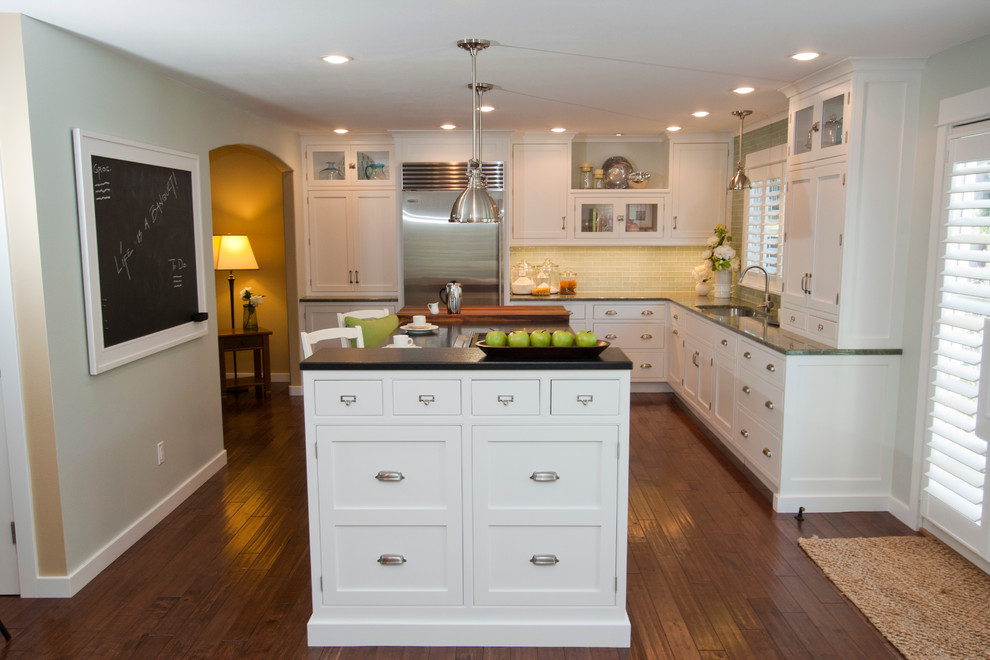 Eat-in kitchen - large traditional l-shaped medium tone wood floor eat-in kitchen idea in Portland with an undermount sink, white cabinets, granite countertops, green backsplash, glass tile backsplash, stainless steel appliances, recessed-panel cabinets and an island