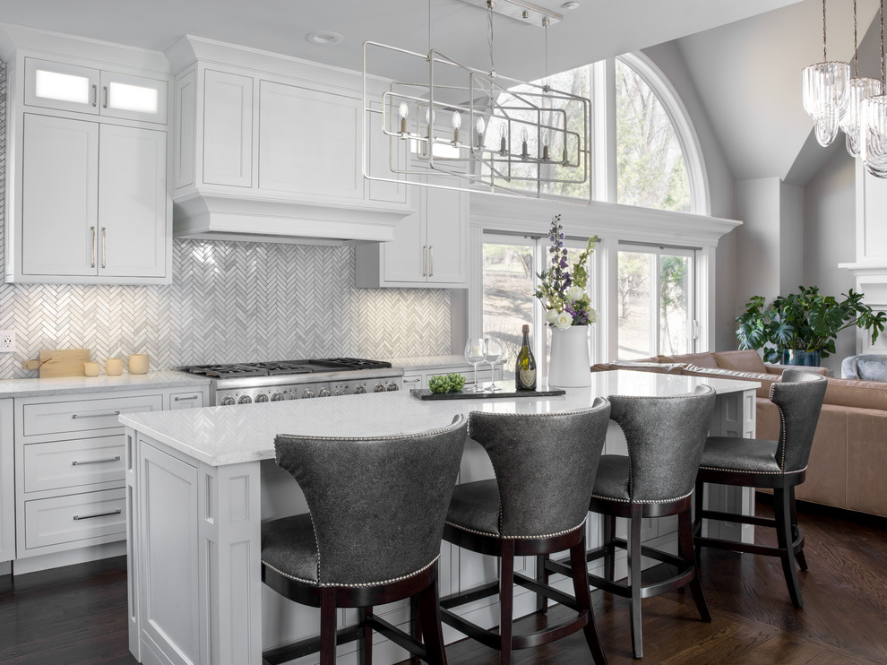 Mid-sized transitional l-shaped dark wood floor and brown floor open concept kitchen photo in Chicago with shaker cabinets, white cabinets, stainless steel appliances, white countertops, marble countertops, white backsplash, mosaic tile backsplash, a farmhouse sink and two islands