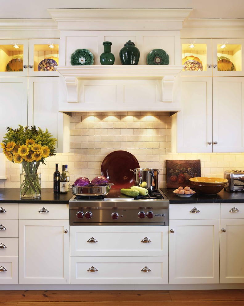 Example of a classic kitchen design in Boston with shaker cabinets, white cabinets, beige backsplash, stainless steel appliances, soapstone countertops and limestone backsplash