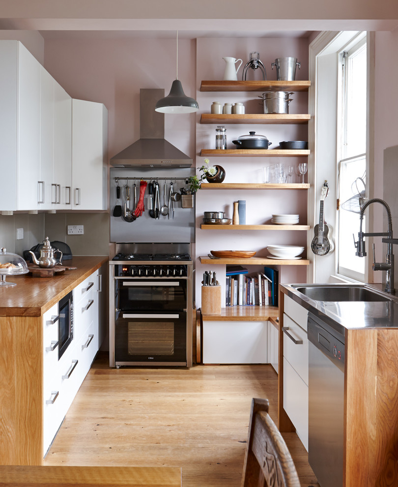 Kitchen - small contemporary medium tone wood floor kitchen idea in London with flat-panel cabinets, white cabinets, wood countertops, gray backsplash, porcelain backsplash, no island and black appliances