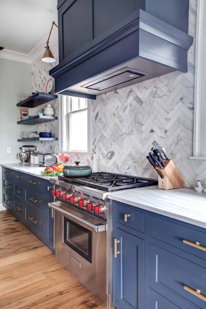 Inspiration for a large transitional l-shaped medium tone wood floor and brown floor eat-in kitchen remodel in New York with an undermount sink, recessed-panel cabinets, blue cabinets, granite countertops, multicolored backsplash, porcelain backsplash, stainless steel appliances, an island and gray countertops