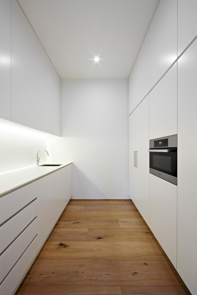 Inspiration for a small scandinavian galley light wood floor enclosed kitchen remodel in Melbourne with flat-panel cabinets, white cabinets and paneled appliances