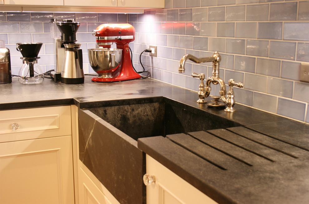 Kitchen - contemporary kitchen idea in Boston with soapstone countertops, a farmhouse sink and blue backsplash