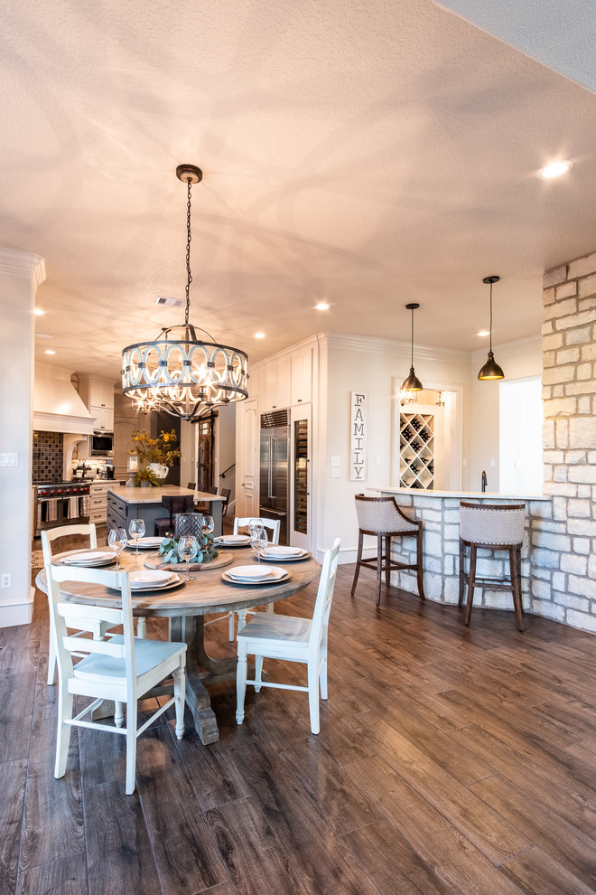 Inspiration for a large galley porcelain tile and brown floor eat-in kitchen remodel in Houston with a farmhouse sink, shaker cabinets, white cabinets, quartzite countertops, multicolored backsplash, stone tile backsplash, stainless steel appliances, an island and multicolored countertops