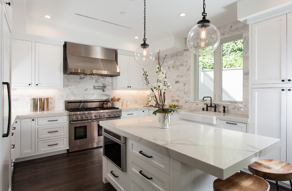 Example of a transitional u-shaped dark wood floor and brown floor enclosed kitchen design in Orange County with a farmhouse sink, shaker cabinets, white cabinets, white backsplash, stainless steel appliances and an island