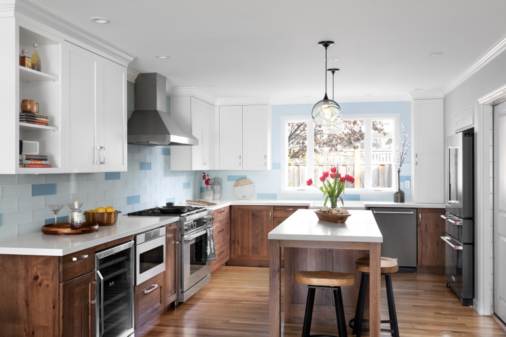 Mid-sized transitional u-shaped medium tone wood floor and yellow floor open concept kitchen photo with a farmhouse sink, recessed-panel cabinets, quartz countertops, blue backsplash, glass tile backsplash, stainless steel appliances, an island, white countertops and medium tone wood cabinets