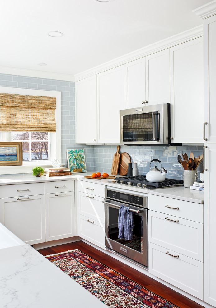 Example of a mid-sized transitional galley dark wood floor and brown floor enclosed kitchen design in Baltimore with a farmhouse sink, shaker cabinets, white cabinets, quartz countertops, blue backsplash, ceramic backsplash and stainless steel appliances