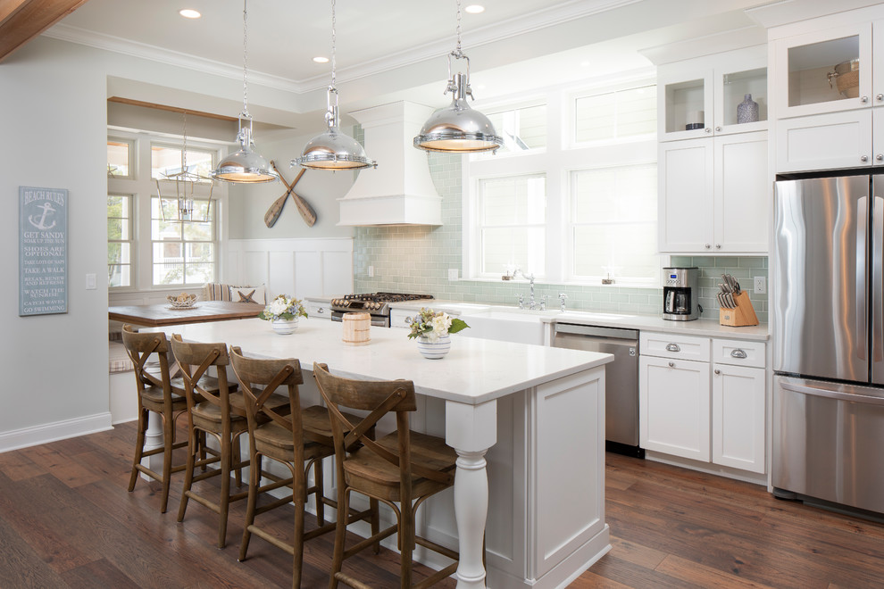 Inspiration for a mid-sized coastal galley dark wood floor and brown floor kitchen remodel in New York with a farmhouse sink, shaker cabinets, white cabinets, quartzite countertops, green backsplash, glass tile backsplash, stainless steel appliances, an island and white countertops