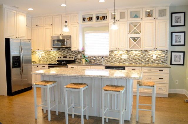 Open concept kitchen - mid-sized beach style single-wall porcelain floor open concept kitchen idea in Jacksonville with an undermount sink, raised-panel cabinets, beige cabinets, quartzite countertops, stainless steel appliances and an island