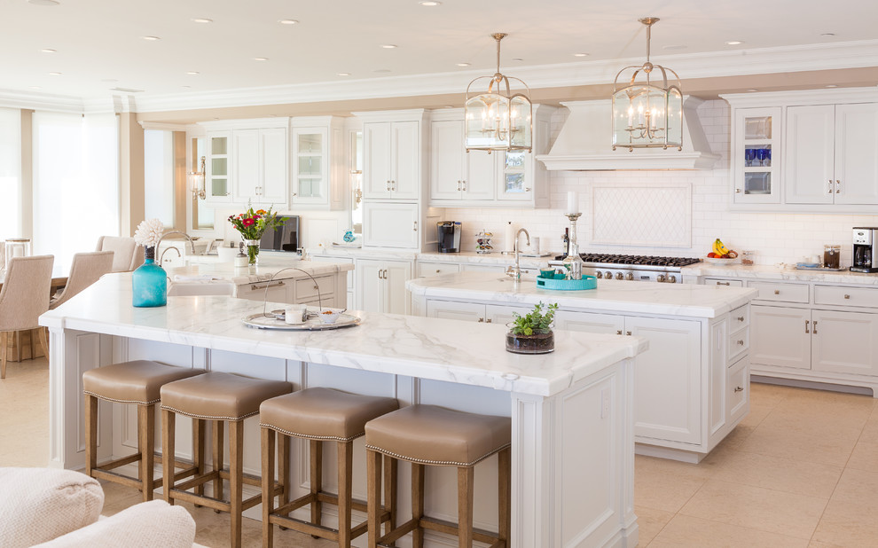 Kitchen - coastal kitchen idea in Orange County with white cabinets and two islands