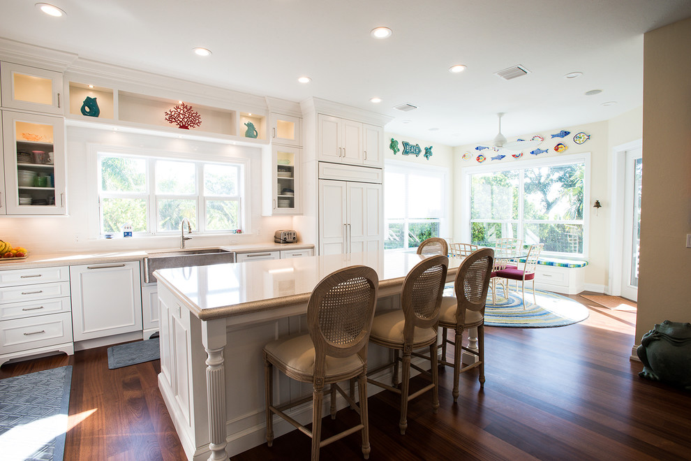 Mid-sized beach style u-shaped medium tone wood floor eat-in kitchen photo in Miami with an undermount sink, shaker cabinets, white cabinets, stainless steel appliances and an island