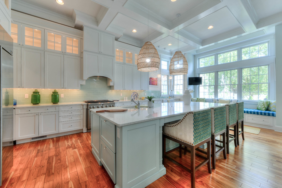Open concept kitchen - coastal medium tone wood floor and brown floor open concept kitchen idea in Philadelphia with an undermount sink, shaker cabinets, white cabinets, green backsplash, glass tile backsplash, stainless steel appliances, an island and white countertops