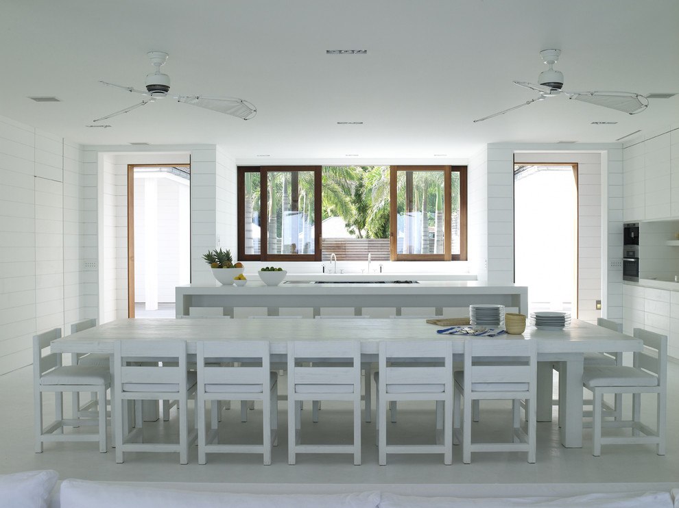 Example of a huge danish l-shaped concrete floor and white floor eat-in kitchen design in London with beaded inset cabinets, white cabinets, white backsplash and quartzite countertops