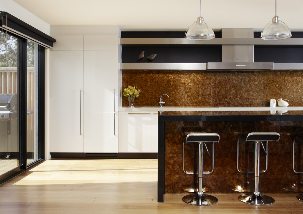 Example of a mid-sized beach style single-wall light wood floor eat-in kitchen design in Melbourne with flat-panel cabinets, white cabinets, brown backsplash, granite countertops, stone slab backsplash, stainless steel appliances and an island